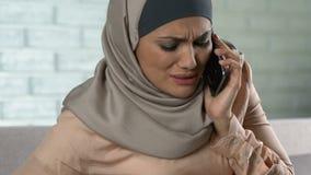 Hembra embarazada preocupada en hijab que llama la emergencia usando el teléfono, contracciones metrajes