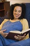 Hembra embarazada que lee un libro Fotografía de archivo
