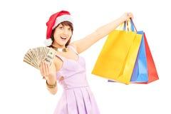 Hembra emocionada con el sombrero de santa que lleva a cabo bolsos y dólares de compras Foto de archivo