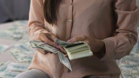 Hembra emocionada que cuenta el paquete de dólares que los lanzan para arriba, ganando la lotería almacen de video