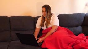 Hembra en casa que trabaja en el ordenador portátil en el sofá delante de TV, forma de vida digital del nómada