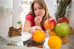 Hembra en dieta en dilema si comer la torta de chocolate o el orang Imagen de archivo libre de regalías