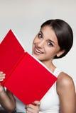 Hembra en el equipo ocasional que sostiene el libro rojo Fotografía de archivo