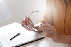 Hembra en el paño casual que sostiene los vidrios con la nota de los documentos sobre la tabla imágenes de archivo libres de regalías