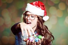 Hembra en el sombrero y los vidrios de Papá Noel que juegan con Foto de archivo libre de regalías