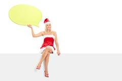 Hembra en el traje de Papá Noel que lleva a cabo una burbuja del discurso Imagenes de archivo