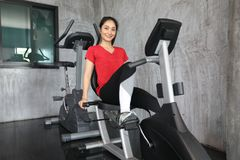 Hembra en la bici del gimnasio que hace ejercicio cardiio imagenes de archivo