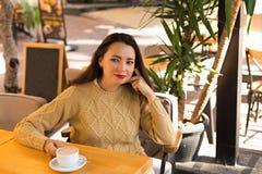 Hembra en suéter caliente en café al aire libre que bebe el chocolate caliente Imagen de archivo libre de regalías