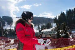 Hembra en traje de esquí, con el casco y las gafas del esquí poniendo en guante Fotografía de archivo libre de regalías