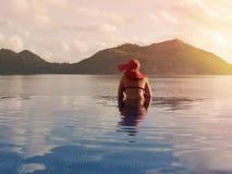Hembra en un sombrero rojo en la piscina contra el contexto de montañas y del océano Seychelles tropicales Isla Praslin Imagen de archivo