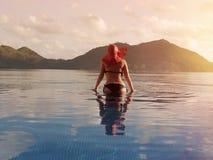 Hembra en un sombrero rojo en la piscina contra el contexto de montañas y del océano Seychelles tropicales Isla Praslin Fotografía de archivo