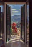 Hembra en una silla en el balcón Foto de archivo libre de regalías