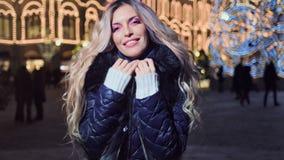 Hembra encantadora en la sonrisa al aire libre de la tarde de la Navidad en el fondo de la decoración del bokeh de la iluminación almacen de metraje de vídeo