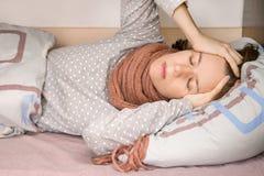 Hembra enferma con el dolor de cabeza que lleva a cabo su cabeza que miente en una cama en casa foto de archivo libre de regalías