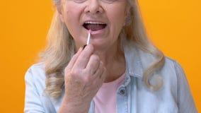 Hembra envejecida feliz que aplica el lustre rosado del labio, preparándose para el acontecimiento, maquillaje de la cara almacen de metraje de vídeo