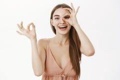 Hembra europea apacible juguetona en el vestido de moda beige que hace gesto aceptable sobre ojo y que hace pis a través del aguj imagen de archivo
