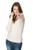 Hembra expresiva con el teléfono celular que señala en usted Foto de archivo libre de regalías