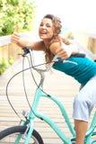 Hembra feliz con la bicicleta que sonríe dando los pulgares para arriba foto de archivo libre de regalías