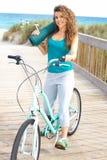 Hembra feliz con la bicicleta que sonríe sosteniendo la estera de la yoga fotos de archivo