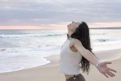 Hembra feliz en la playa que lanza sus brazos detrás Foto de archivo libre de regalías