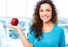 Hembra feliz hermosa que sostiene una manzana imagen de archivo libre de regalías