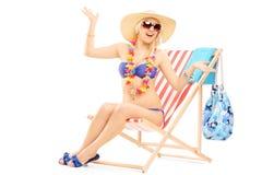 Hembra feliz joven con un sombrero que presenta en una silla de playa Imagenes de archivo