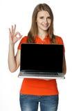 Hembra feliz que muestra una pantalla de la computadora portátil y que gesticula OK Fotografía de archivo libre de regalías