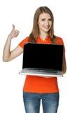 Hembra feliz que muestra una pantalla de la computadora portátil y que gesticula el pulgar para arriba Imagenes de archivo