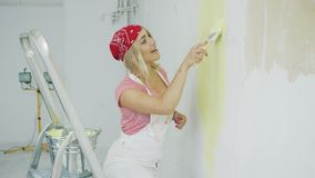 Hembra feliz que sumerge el cepillo en pintura de la pared almacen de metraje de vídeo