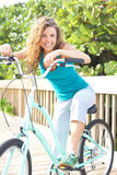 Hembra feliz que toma una rotura en paseo marítimo con la bicicleta fotografía de archivo libre de regalías