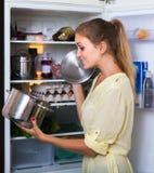 Hembra hambrienta que coloca el refrigerador cercano con la cacerola de comida Foto de archivo