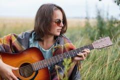Hembra hermosa con el peinado corto que lleva las gafas de sol elegantes que descansan al aire libre tocando la guitarra que disf Foto de archivo