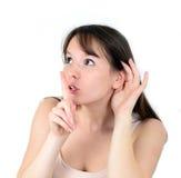 Hembra hermosa con escuchar mientras que sostiene el finger en la GE de la boca Fotos de archivo