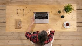 Hembra hermosa del freelancer que presenta y que trabaja en línea con las auriculares con el mic en una mesa o un hogar de la peq almacen de video