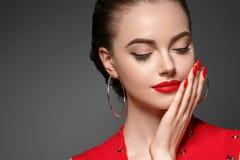 Hembra hermosa del pelo del curle en rojo con los labios y la manicura rojos del vestido, rojo de la belleza fotos de archivo libres de regalías