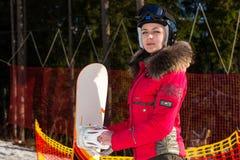 Hembra hermosa en traje de esquí, casco y las gafas del esquí que colocan los wi Foto de archivo