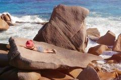 Hembra hermosa en una piedra grande contra el mar en las Seychelles Imágenes de archivo libres de regalías