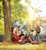 Hembra hermosa joven en parque que lee un libro y que come la manzana Fotografía de archivo