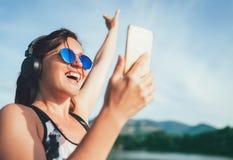 Hembra hermosa joven que activa y que escucha la música usando el smartphone y los auriculares inalámbricos que sonríen alegre El imagenes de archivo