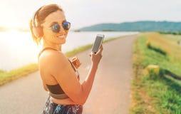 Hembra hermosa joven que comienza activar y que escucha la música usando smartphone y auriculares inalámbricos que sonríen alegre imagen de archivo