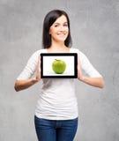 Hembra hermosa que muestra una tableta con una manzana Imagen de archivo