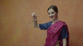 Hembra india atractiva en la sari que muestra karatalas