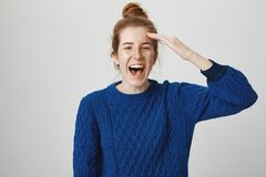 Hembra joven atractiva joven del pelirrojo en suéter cómodo del invierno que saluda con la palma cerca de la frente, riendo hacia Fotos de archivo libres de regalías