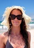 Hembra joven atractiva en la playa con el sombrero Foto de archivo