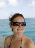 Hembra joven atractiva que sonríe con las gafas de sol encendido Fotografía de archivo libre de regalías
