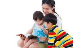 Hembra joven con dos pequeños niños asiáticos que leen un libro imágenes de archivo libres de regalías