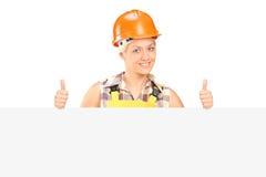Hembra joven con el casco que presenta detrás de un panel con los pulgares para arriba Foto de archivo libre de regalías