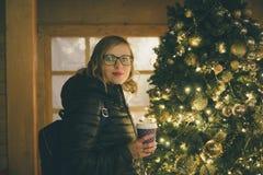 Hembra joven con la bebida caliente contra árbol de los Años Nuevos Foto de archivo
