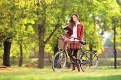 Hembra joven con la bicicleta en un libro de lectura del parque Foto de archivo libre de regalías