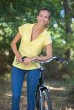 Hembra joven con la bicicleta que vaga en bosque Imagen de archivo